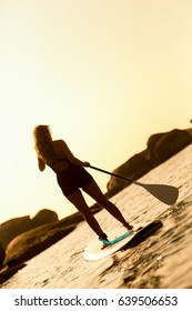Girl on stand up paddle board in the sunset