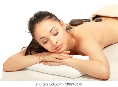 Girl on a stone therapy, hot stone massage. Isolated on white.