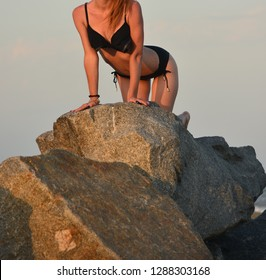 The girl on the stones can see the sea and the sky of the face is not visible is on all fours