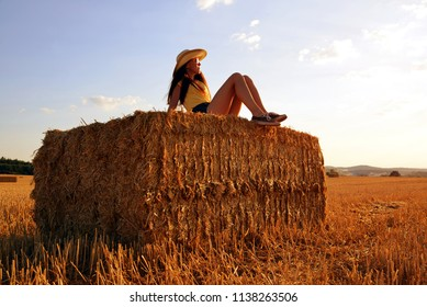 Girl on a straw bale in the field at sunset.