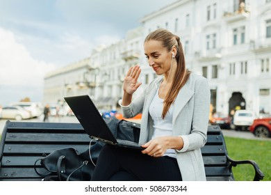 """the girl on the street communicates on Skype. on the street good weather also shines the sun. she shows to the interlocutor """"hi"""" and very joyfully smiles."""