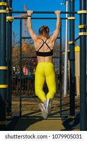 Girl on street workout. She pull-ups herself up on bar on sports ground in park. Photo from the back in full growth. Man is unrecognizable.