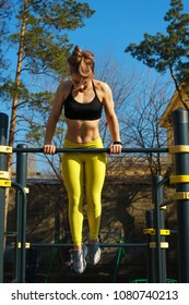 Girl on street workout. She pull-ups herself up on bar on sports ground in park. Work of hands and back.