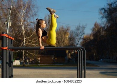 Girl on street workout. She does gymnastic exercises on parallel crossbars. Girl is dressed in a black topic and yellow sports pants.