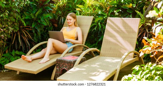 Girl on the sunbed working on a laptop, banner panorama