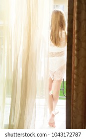 girl on a Sunny morning looking out the window