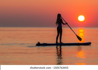 Girl on sup board with beautiful colored sunrise background