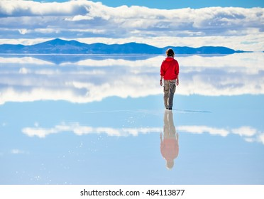 Girl on surface of salt lake Salar de Uyuni in Bolivia with sky reflection