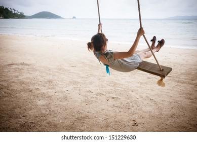 Girl on a swing on a beach