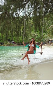 girl on swing at tropical sea beach