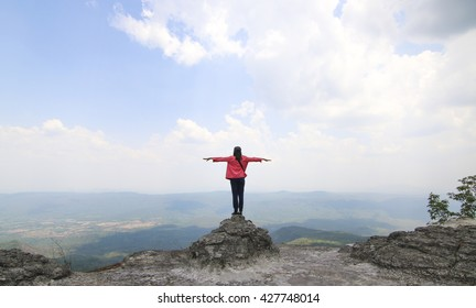 Girl on the top of a boulder