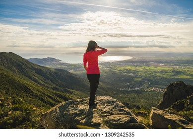 Girl on top of a cliff admiring the beautiful landscape view, in the middle of nature, in Catalonia, Spain