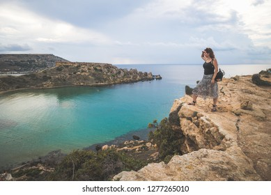 Girl on top of a cliff watching and admiring the sea view, Malta