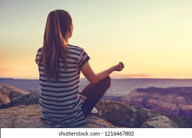 A girl on top of a hill in silence and loneliness admires a tranquil natural landscape in search of a soul. Or she practices yoga and meditation.