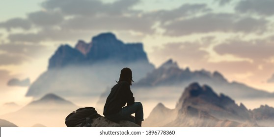 A girl on top of a hill in silence admires tranquil landscape in evening.