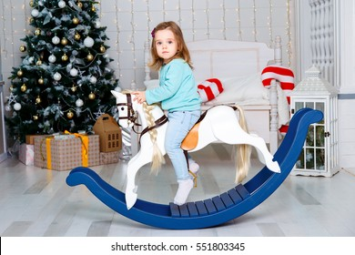 girl on a toy horse near a Christmas tree. new Year.Christmas tree
