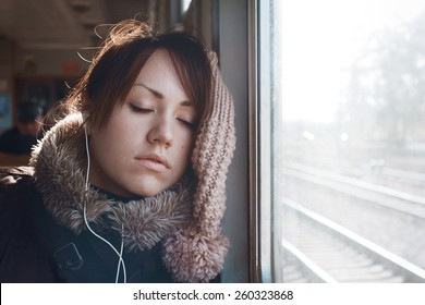Girl on train. Portrait of sleeping girl, listening to music on headphones. Beautiful brunette in warm clothing