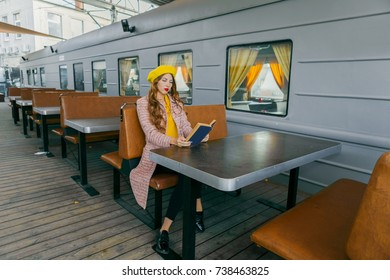 Girl on the train station, reading a book and waiting for a train. Wearing coat and yellow beret. Autumn concept.