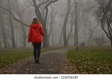 Girl on a walk in the park, thick fog, red jacket on the girl