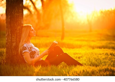 girl on a warm summer afternoon enjoying a good book sitting on the grass in the park, leaning against a tree.