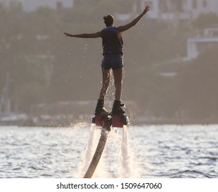 Girl on a water attraction at sea. Flyboard