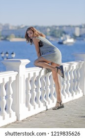 Girl on the waterfront in morning time. Tall female person in gray short dress and fishnet stockings climbs over a fence