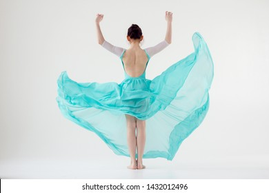 A girl on a white background in a beautiful blue dress that flutters in motion with an open back