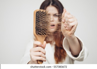 girl on a white background with a comb for the hair, the hair problem