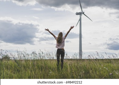 girl on a windmill background, summer windmills, sunset. Wind turbine, wind power. wind power plant