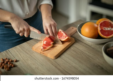 girl on a wooden board cuts with a knife a juicy vitamin orange