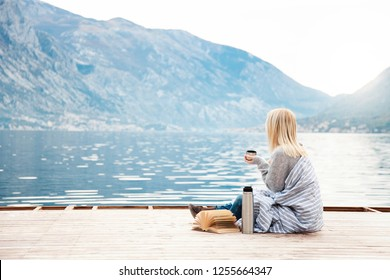 Girl on wooden pier by winter sea, mountains. Cozy picnic with hot beverages, tea, coffee or cocoa in thermos and mug, warm plaid, opened book. Concept of enjoying nature, relaxation, reading on beach