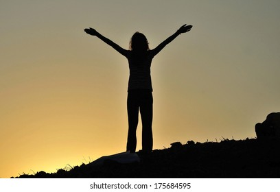 Girl with open arms at the sunset