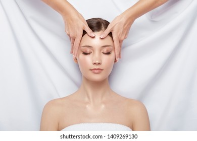 girl with open shoulders having facial massage on white background, face treatment, spa procedures, woman receiving relaxation
