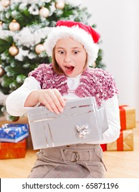 Girl opening Christmas gift box with very surprised facial expression