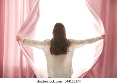 Girl opening curtains