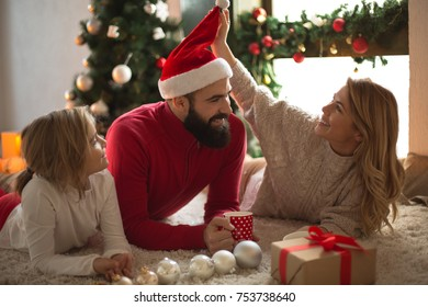 Girl opening a present on a Christmas morning with family