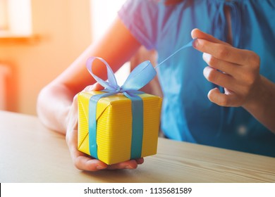 girl opening surprise gift box with ribbon