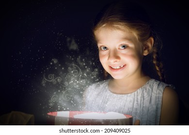 girl opens a box of magic, sorcery, and there shines the light, Christmas miracle