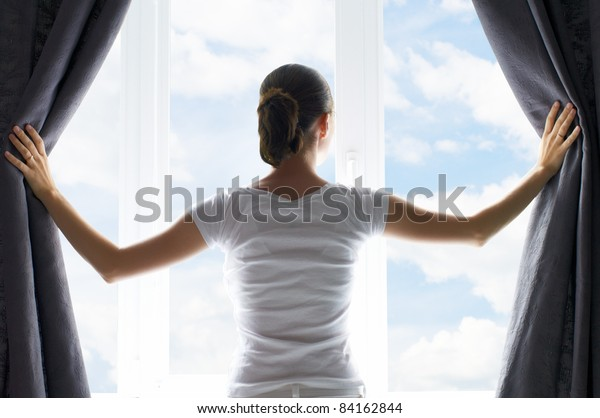 Mädchen öffnet die Vorhänge
