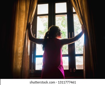 Girl opens the curtains at window