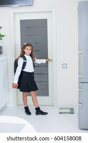Girl opens the door and goes to school with a backpack and an apple. Girl in the kitchen going to school
