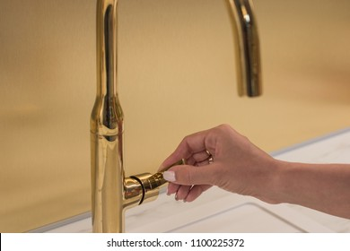 The girl opens the faucet for washing hands