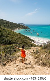 girl with orange beach dress with arms wide open looking towards the beautiful and famous prainhas beach in pontal do atalaia, arraial do cabo, rio de janeiro, brazil