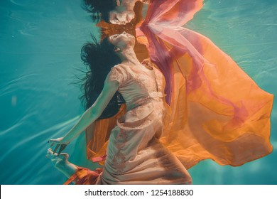girl with orange dress is dreamy and meditative floating under water, like the soul before reincarnation