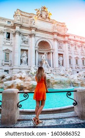 Girl in orange dress in front of Trevi Fountain, Young pretty girl with blonde hair in a orange/ yellow dress. Beautiful woman near Trevi Fountain, Rome, Italy. Happy girl enjoy the vacation holiday.