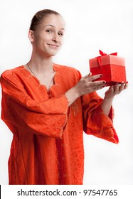 The girl in orange dress with a gift studio photography