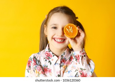 the girl with an orange half fruit on a yellow background