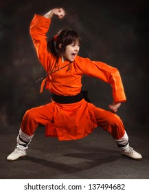 girl in an orange suit performs the form of martial arts with a shout