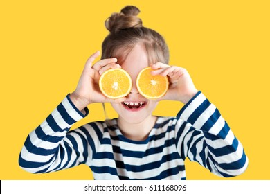 Girl with oranges on the background in the studio