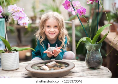 The girl in the orchid greenhouse is played with flowers and stones. Girl with blooming pink orchids holds stones